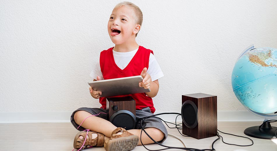 Boy with down syndrome sits crossed leg on the floor, playing music from an Ipad.