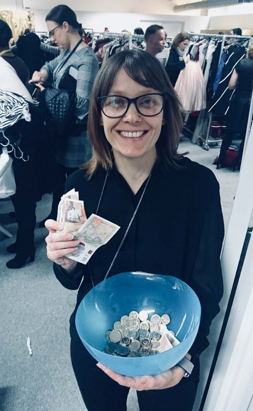 Picture of Heidi at the sample sale, holding a bowl of money.