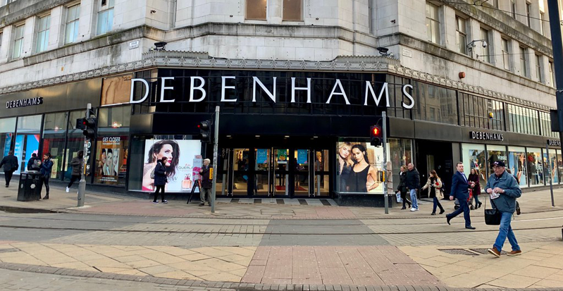 A picture of a Debenhams store on a street corner, with people walking past it.