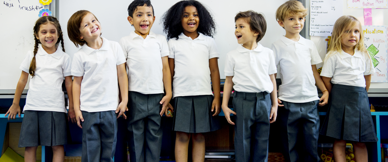 A group of primary school children in white polo shirts and grey skirts and trousers stand in front of their classroom board smiling at the camera.