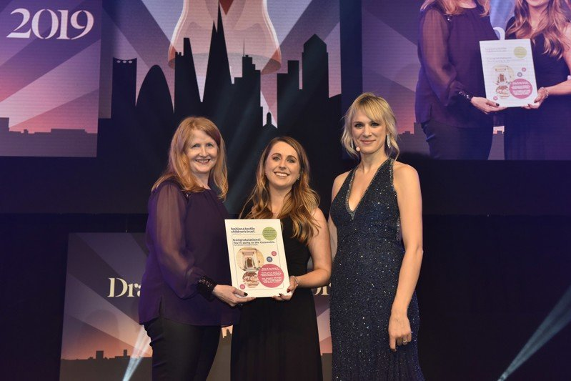 Prize draw winner Suzanne collecting her prize on stage with Anna and Kirsty.