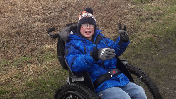 Picture of Robyn in his wheelchair, funded by an FTCT grant.