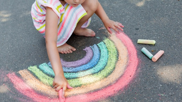 Picture of a child drawing a rainbow in chalks on a pavement.