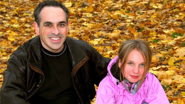 Picture of James and Emma sitting in the autumn leaves.