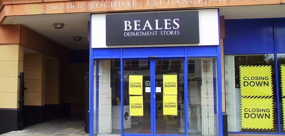 A Beales store stands empty with signs advertising a closing down sale.