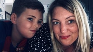 Mairead, a white woman with blond hair holds the camera smiling. She is photographed next to her son Jed who has brown hair.