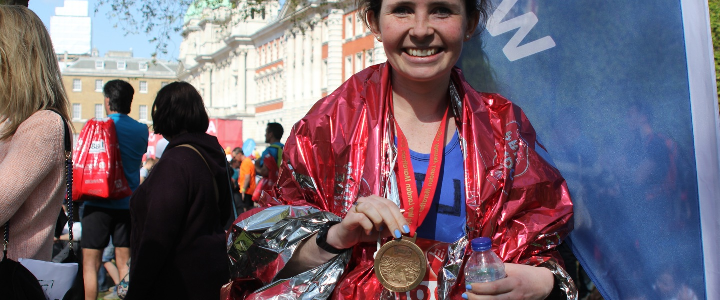 Picture of a female FTCT Marathon runner with her medal.