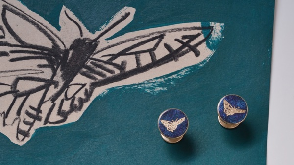 Hand drawn butterfly sketched on a blue background, next to some cufflinks.