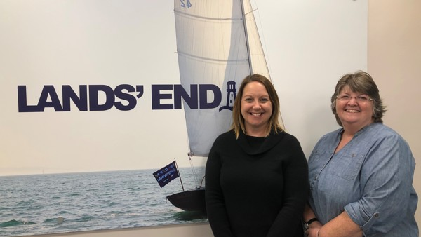 A picture of Wendy and HR manager Sarah in front of the Lands End logo.