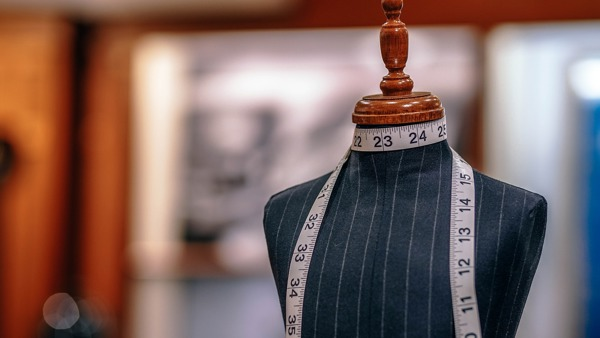 A black and white strped tailors dummy sits in a shop with a tape measure around the neck.