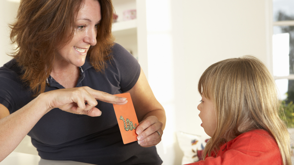 Women shows a alphabet card to a child with down syndrome, during a speech therapy session.