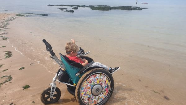 Ned sits in his new wheelchair at the waters edge