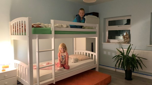 Liliana and Marcel sit on their new bunkbeds in their bedroom