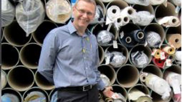 Glyn standing in front of some rolls of fabric at the factory.
