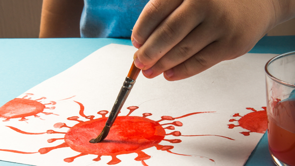 A child in a blue tshirt paints a coronavirus cell in red paint.