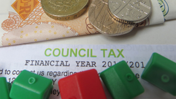 Picture of a council tax bill next to red and green monopoly houses and money.