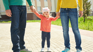 Family in colourful jumpers hold an infants hand